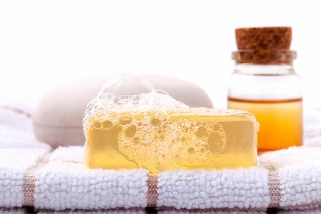 Jabón herbario del balneario en la toalla de baño blanca con el aislante de la miel en el fondo blanco.