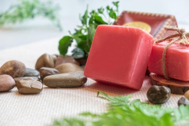 Jabón de hierbas hecho a mano natural color rojo con piedra de la hoja de la naturaleza en la iluminación del sol paño marrón