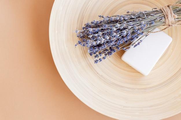 Jabón de lavanda artesanal. barra de jabón natural con flores de lavanda secas en placa de bambú con espacio de copia. cosméticos orgánicos para el cuidado de la piel y spa.