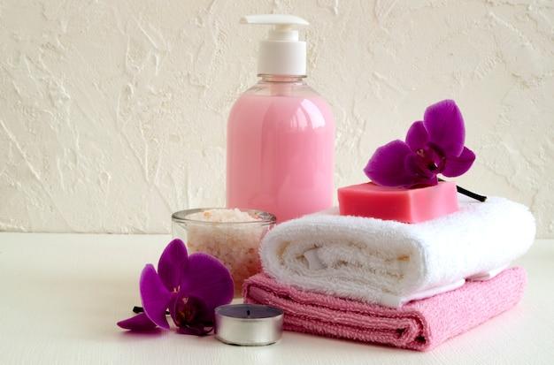 Jabón líquido y dos toallas sobre un fondo blanco.