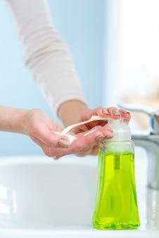 Jabón líquido verde y agua para lavarse las manos.