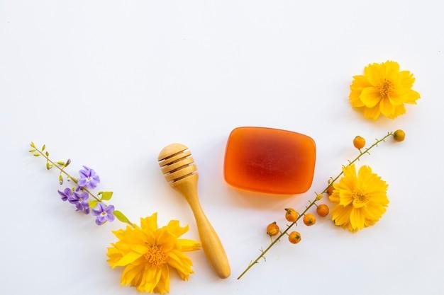 Jabón de miel para el cuidado de la piel junto a flores.