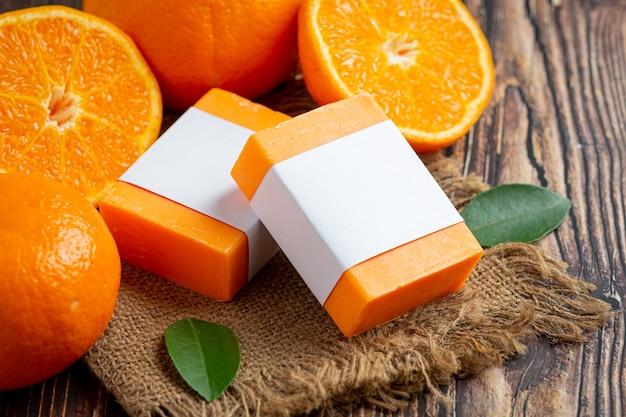 Jabón de naranja con naranja fresca sobre fondo de madera oscura.