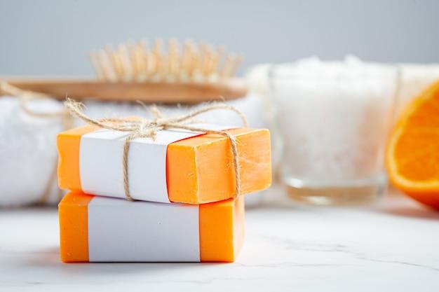 Jabón de naranja con naranja fresca sobre fondo de mármol