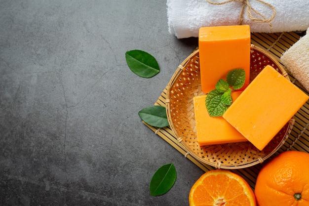 Jabón de naranja con naranja fresca sobre fondo oscuro