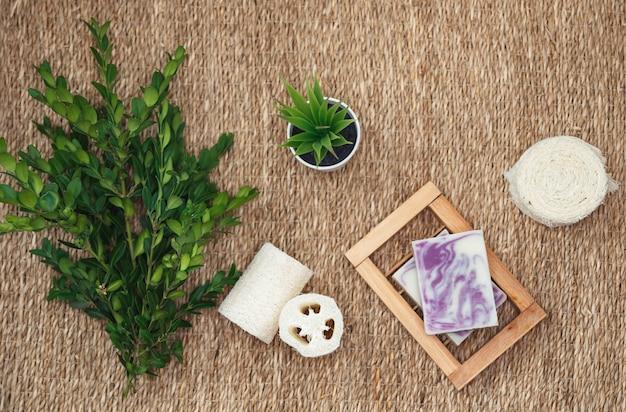 Jabón natural artesanal y complementos para el cuidado corporal. varios objetos relacionados con el spa sobre fondo de paja