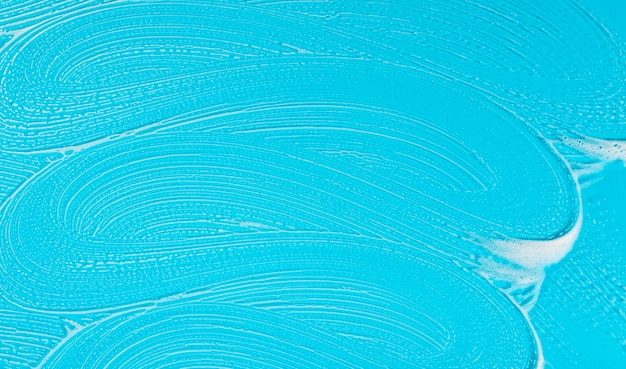 Jabón plano en espuma sobre fondo azul.
