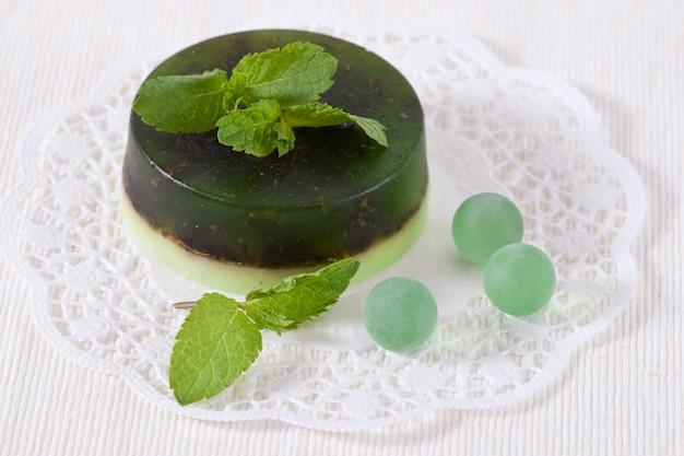 Jabón verde hecho a mano y hojas de menta en blanco.