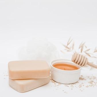 Jabones miel; cucharón de miel y esponja vegetal en superficie blanca