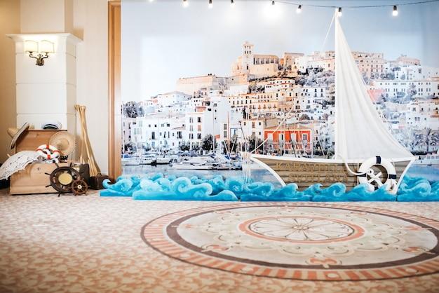 Jacht de madera decorativo se encuentra ante una imagen de puerto de mar en la pared