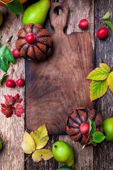 Jack-o-lantern alrededor de la tabla de cortar vacía en madera. otoño víspera de todos los santos. vista superior. copyspace cuadro.