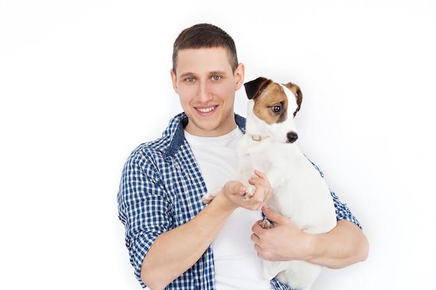 Jack russell terrier. un hombre sonriente que sostiene un perro en un blanco. un joven con amor tiene un perro en sus brazos y juega con él, sobre un fondo blanco. amistad entre un perro y su dueño.