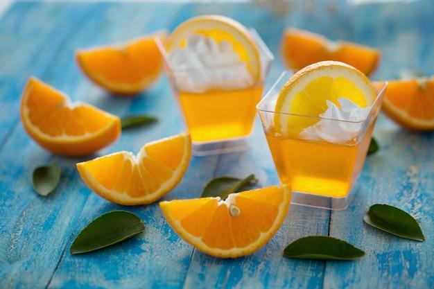 Jalea de naranja en una taza con crema batida y naranja en rodajas sobre fondo azul de madera