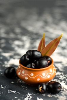 Jambolan ciruela con hojas en un tazón de cerámica