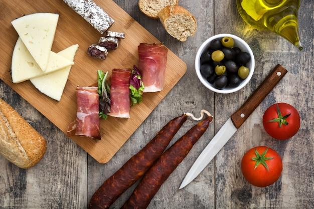 Jamón serrano español, queso y chorizo en mesa de madera
