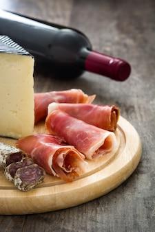 Jamón serrano español con salchichas, queso y vino en mesa de madera