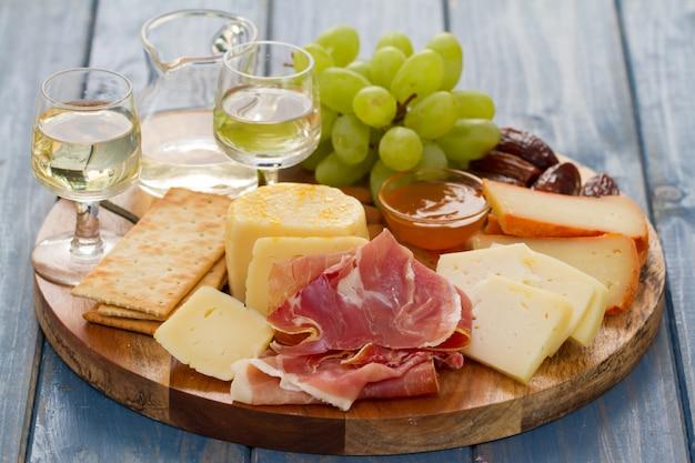 Jamón serrano con queso y vino blanco en tabla de madera sobre mesa de madera azul
