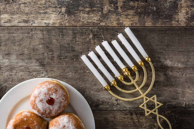 Jánuca judía menorah y sufganiyot donas en mesa de madera