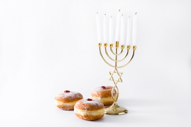 Jánuca judía menorah y sufganiyot donuts en superficie blanca