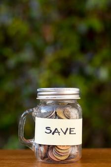 Jar con monedas y guardar la etiqueta con fondo borroso