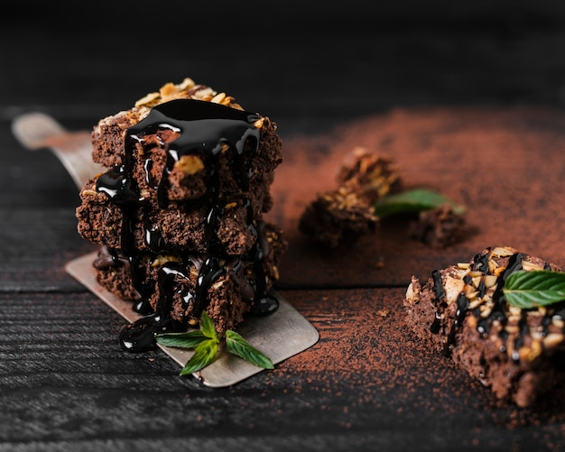 Jarabe de chocolate de alto ángulo vertido sobre la torre de brownies de nueces de chocolate en la bandeja