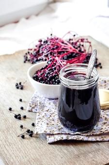 Jarabe de saúco negro casero en frasco de vidrio y racimos de saúco negro
