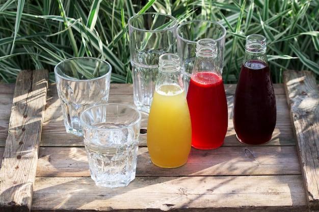 Jarabes de fresa, cereza y ruibarbo y vasos con agua en una mesa de madera en el jardín.