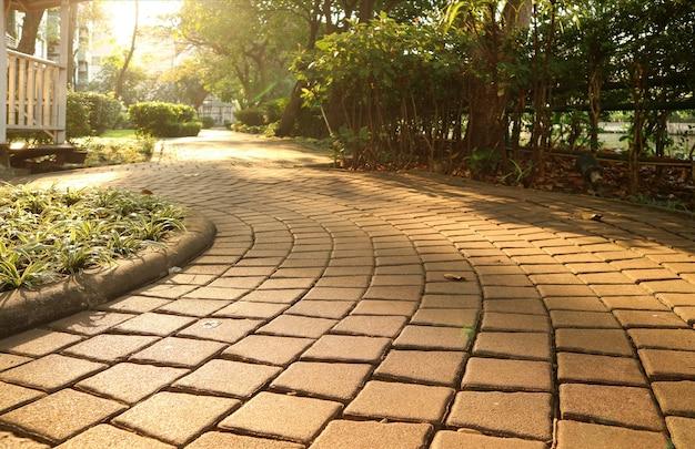 Jardín que curva camino de bloque de piedra en la suave luz del sol
