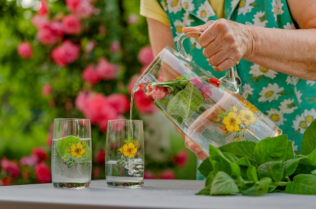 En el jardín de verano de una casa de campo. que tenga un buen fin de semana de verano, relájese refresco (limonada) con menta y hojas de menta, un producto saludable