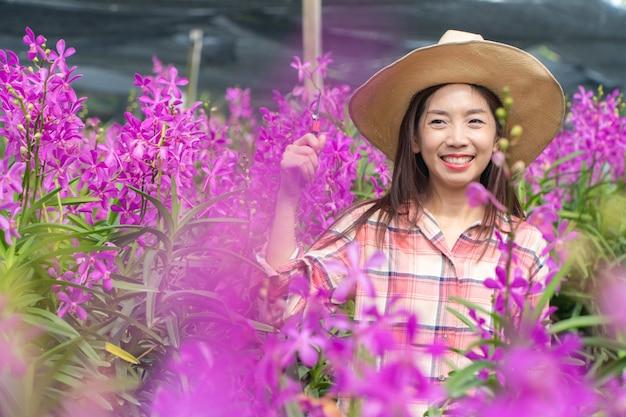 Las jardineras jóvenes usan una camisa a cuadros y un sombrero. manos sosteniendo tijeras para cortar orquídeas y sonrisa.