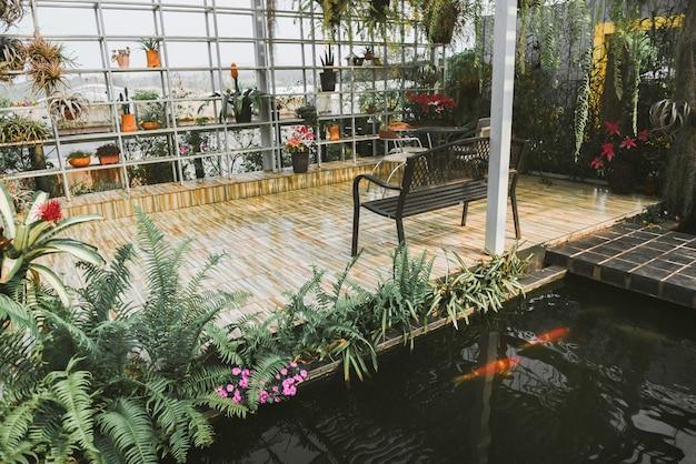 Jardinería doméstica y decoración de ambientes de invernadero en interiores jardín secreto y configuraciones modernas de jardinería flores y plantas y vegetación en espacios de trabajo con mesa y banco