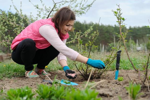 Jardinería de primavera, jardinera trabajando en guantes