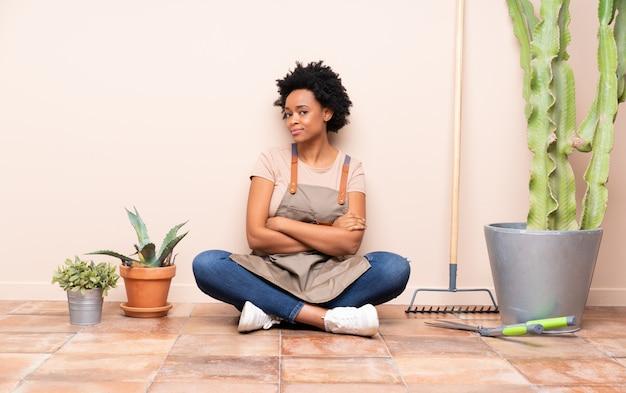 Jardinero afroamericano mujer sentada en el piso