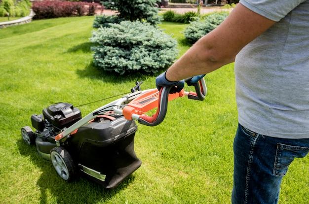 Jardinero cortando el césped. diseño de exteriores. fondo verde