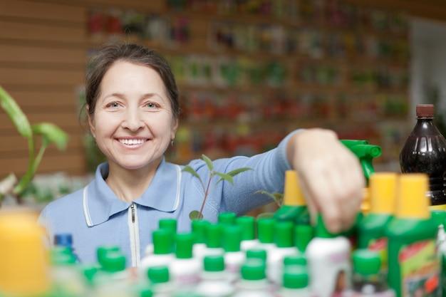 Jardinero elige fertilizante líquido en la tienda