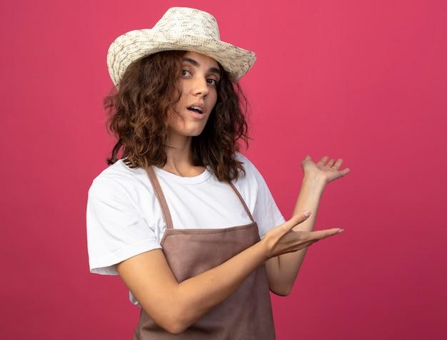 Jardinero femenino joven complacido en uniforme vistiendo puntos de sombrero de jardinería con las manos en la espalda