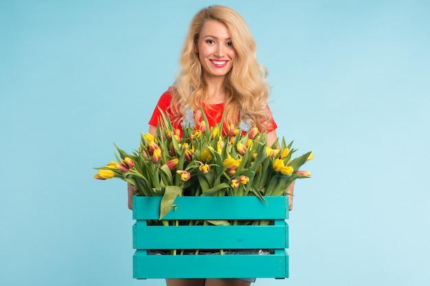 Jardinero de hermosa mujer rubia con caja con tulipanes en la pared azul