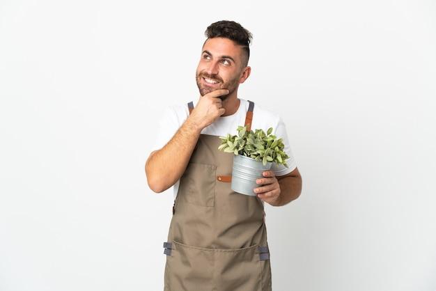 Jardinero hombre sosteniendo una planta sobre fondo blanco aislado mirando hacia arriba mientras sonríe