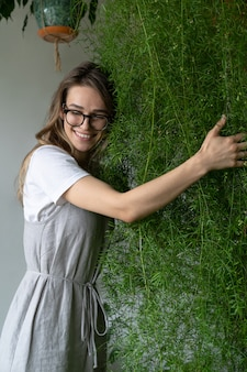 Jardinero joven feliz en vestido de gravamen, abrazando exuberante planta de helecho espárrago en su tienda de flores. vegetación en casa. amor por las plantas. jardín interior acogedor.