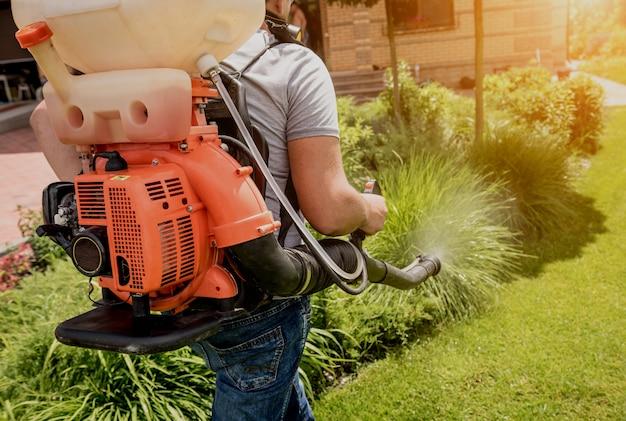Jardinero en máscara protectora y gafas rociando árboles de pesticidas tóxicos
