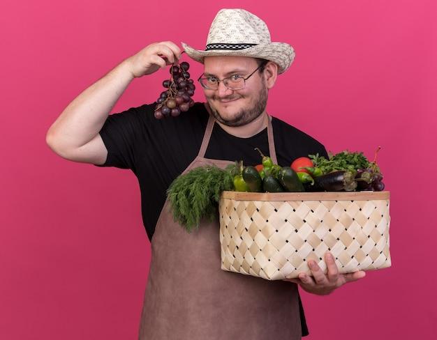 Jardinero masculino joven complacido con sombrero de jardinería sosteniendo canasta de verduras y uvas aisladas en la pared rosa