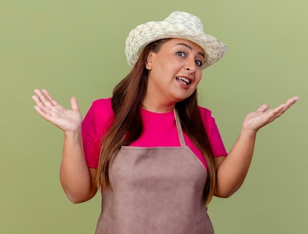 Jardinero de mediana edad mujer en delantal y sombrero confundido extendiendo los brazos