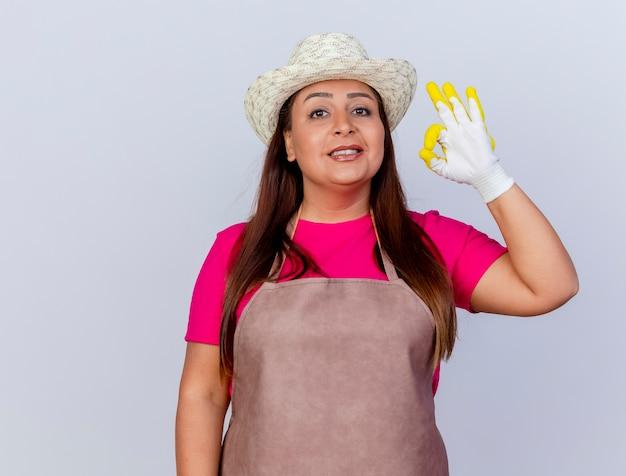 Jardinero de mediana edad mujer en delantal y sombrero con guantes de goma mirando a la cámara mostrando signo ok sonriendo de pie sobre fondo blanco.