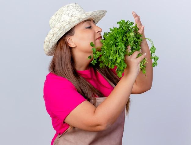 Jardinero de mediana edad mujer en delantal y sombrero sosteniendo hierbas frescas inhalando buen aroma de pie sobre fondo blanco.
