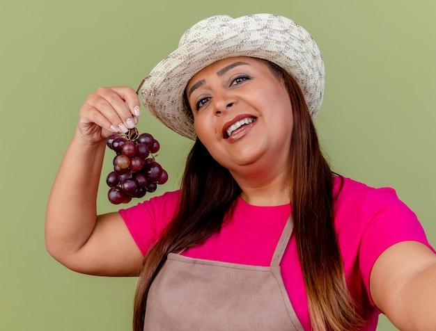 Jardinero de mediana edad mujer en delantal y sombrero sosteniendo racimo de uva con sonrisa