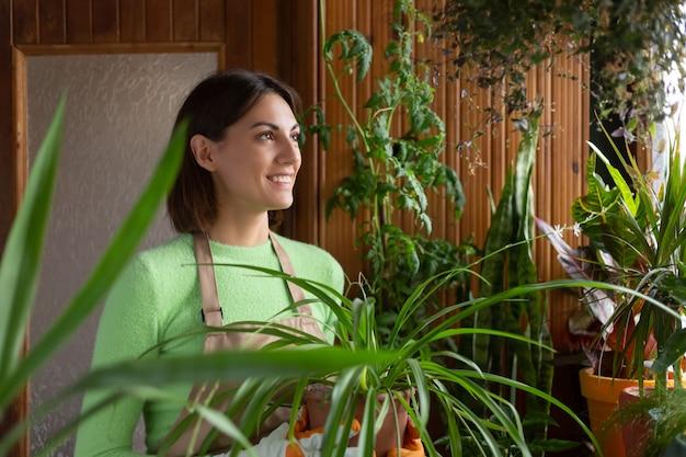 Jardinero de mujer en casa en delantal y guantes con plantas en crecimiento en el balcón de la casa
