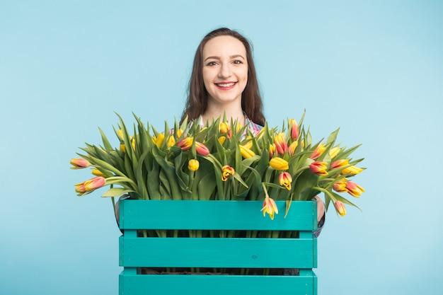 Jardinero mujer hermosa con caja con tulipanes en superficie azul