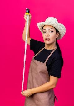 Jardinero de mujer hermosa joven en delantal y sombrero sosteniendo cinta métrica mirando sorprendido de pie