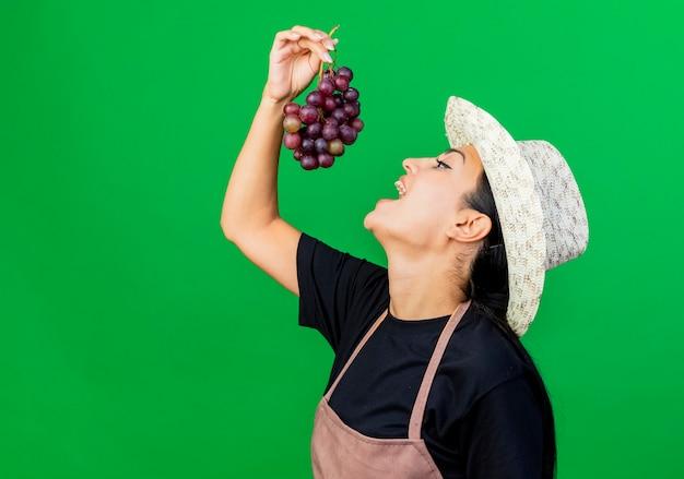 Jardinero de mujer hermosa joven en delantal y sombrero sosteniendo racimo de uva yendo ti comer de pie sobre la pared verde