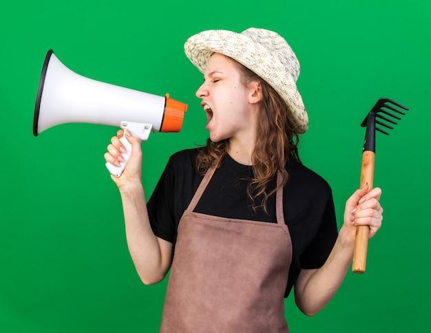 Jardinero mujer joven enojado con sombrero de jardinería sosteniendo rastrillo y habla por altavoz